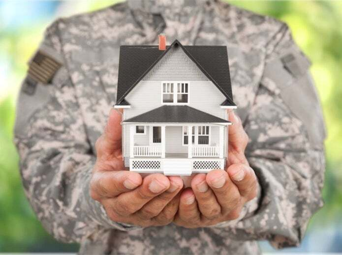 Veteran holding house in palm of hands