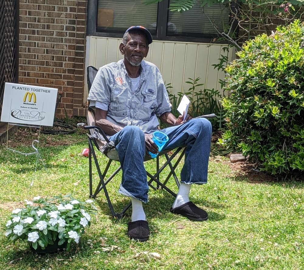 planted together resident  man sitting outside in chair