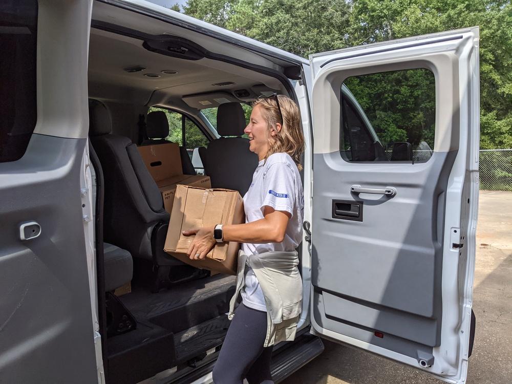 Female volunteer placing box in van