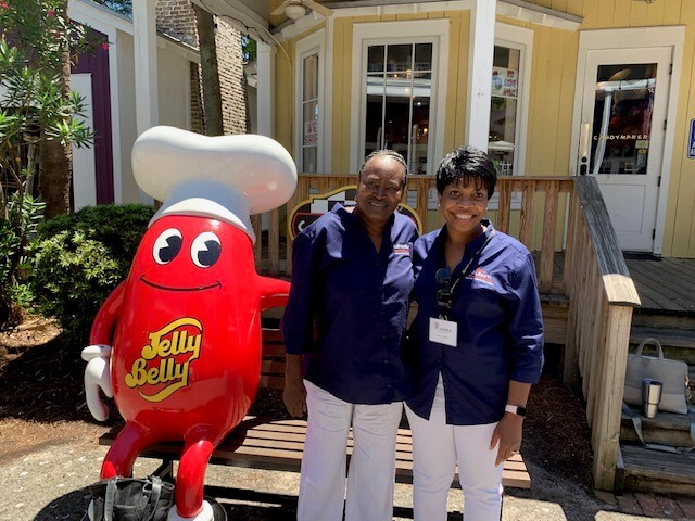 ceo and commissioner posing with jelly bean statue