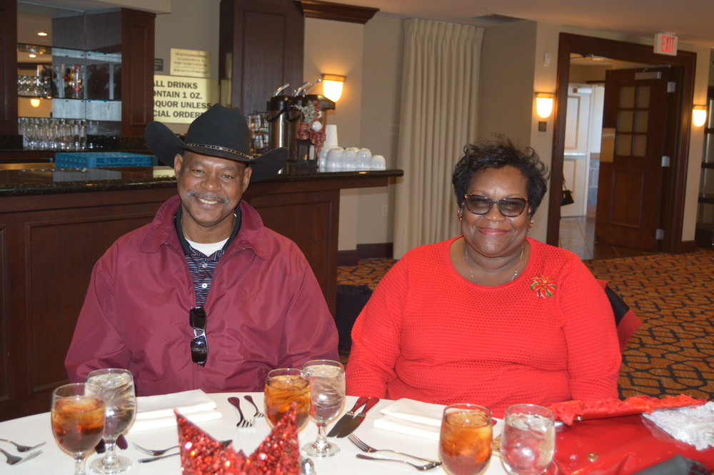 Male and female in red, male with a cowboy hat at table